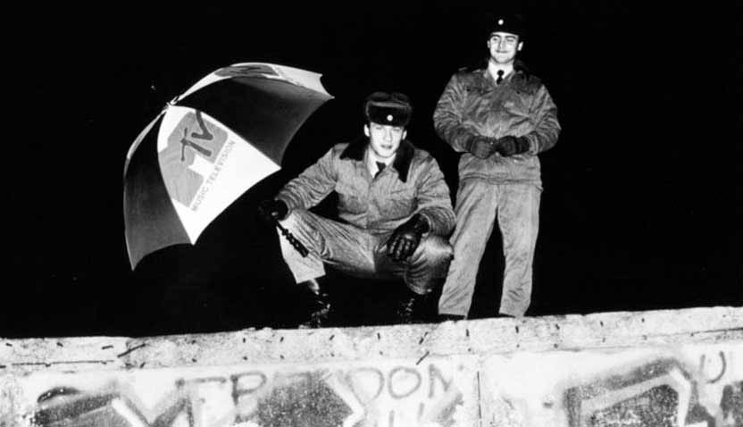 Black and white photo of two men holding a MTV umbrella on a wall, showing media's worldwide cultural impact